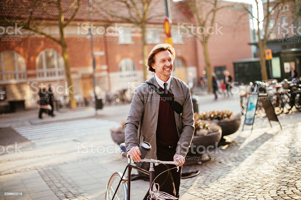 Businessman leading his bicycle through city stock photo