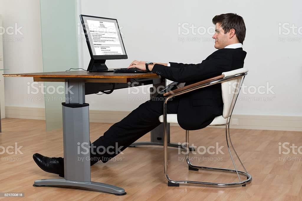 Businessman Leaning Back In His Chair While Working On Computer stock photo