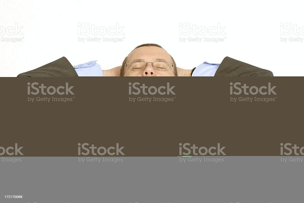 A businessman leaning back in his chair with hands on head royalty-free stock photo