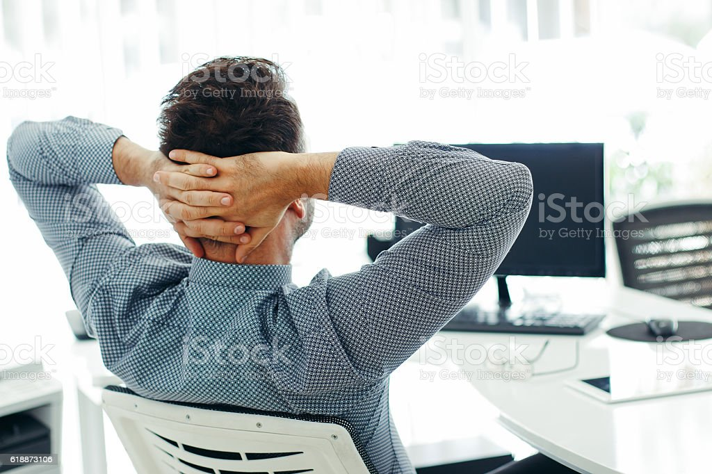 Businessman leaning back in the chair stock photo