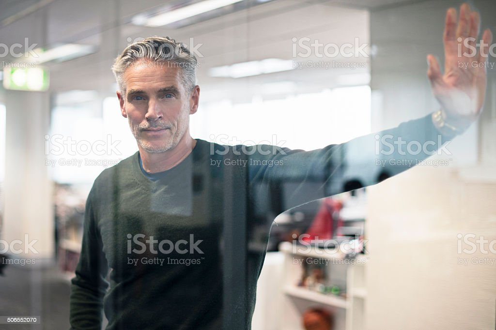 Businessman leaning on a glass in the office stock photo