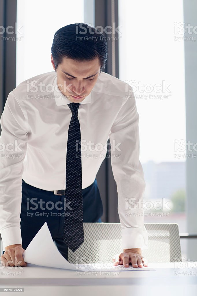 Businessman leaning over table with document planning stock photo