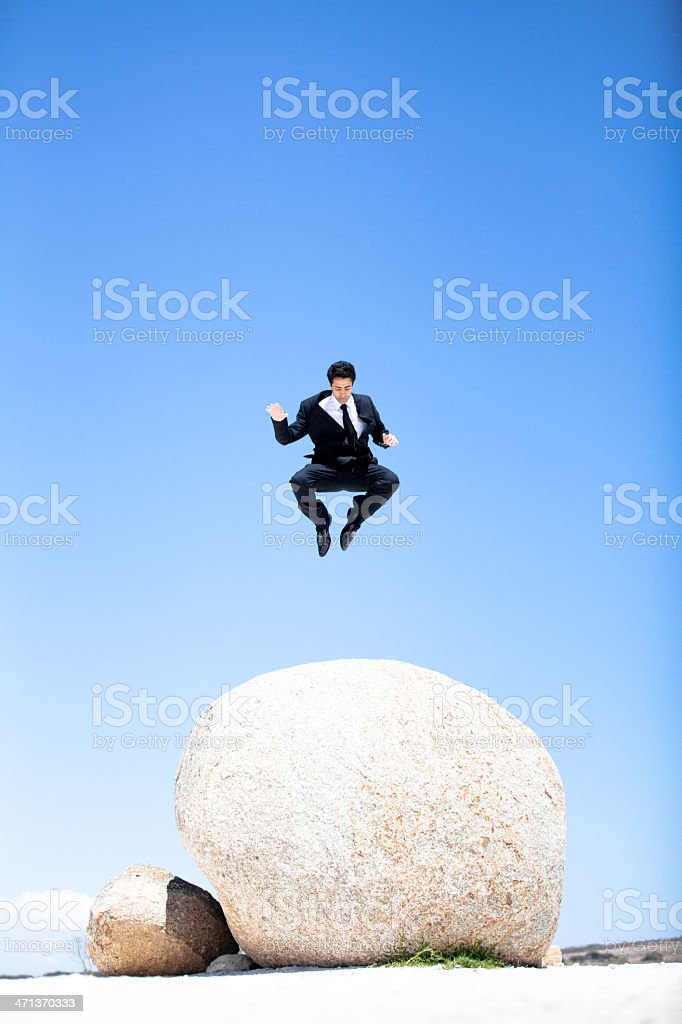 Businessman leaping off a boulder royalty-free stock photo