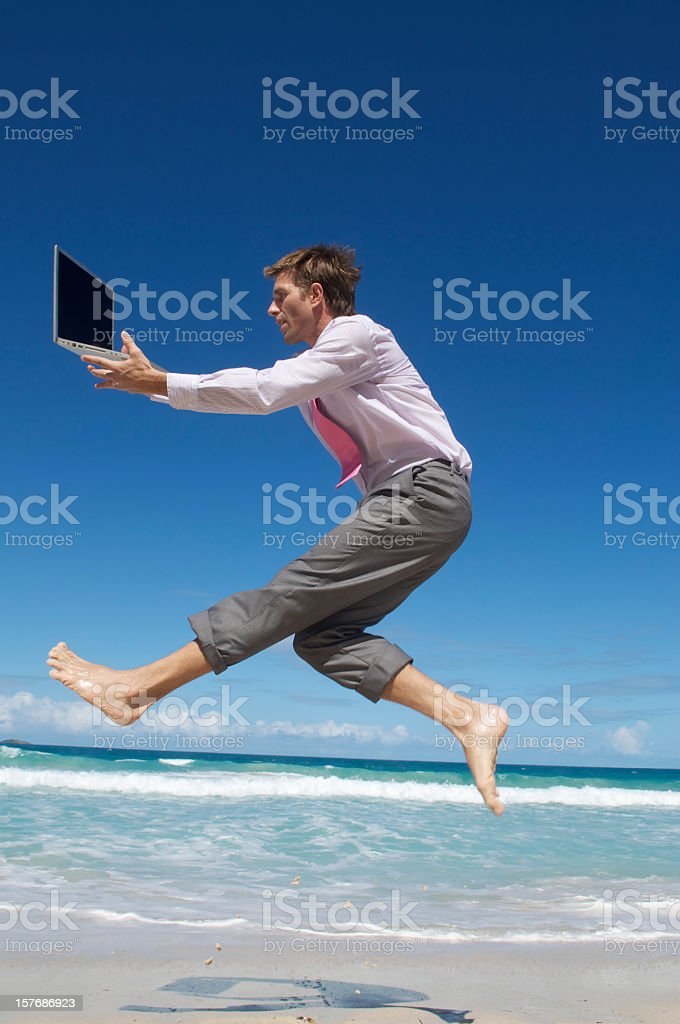 Businessman Leaps Along Shore w Laptop royalty-free stock photo