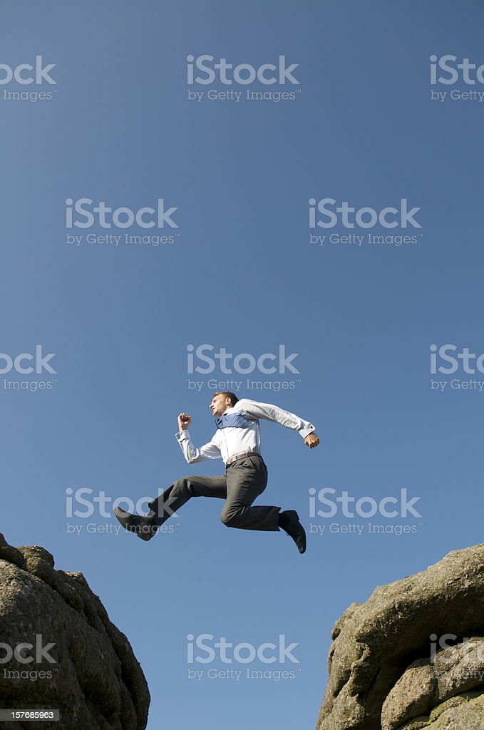 Businessman Leaps Between Big Boulders royalty-free stock photo