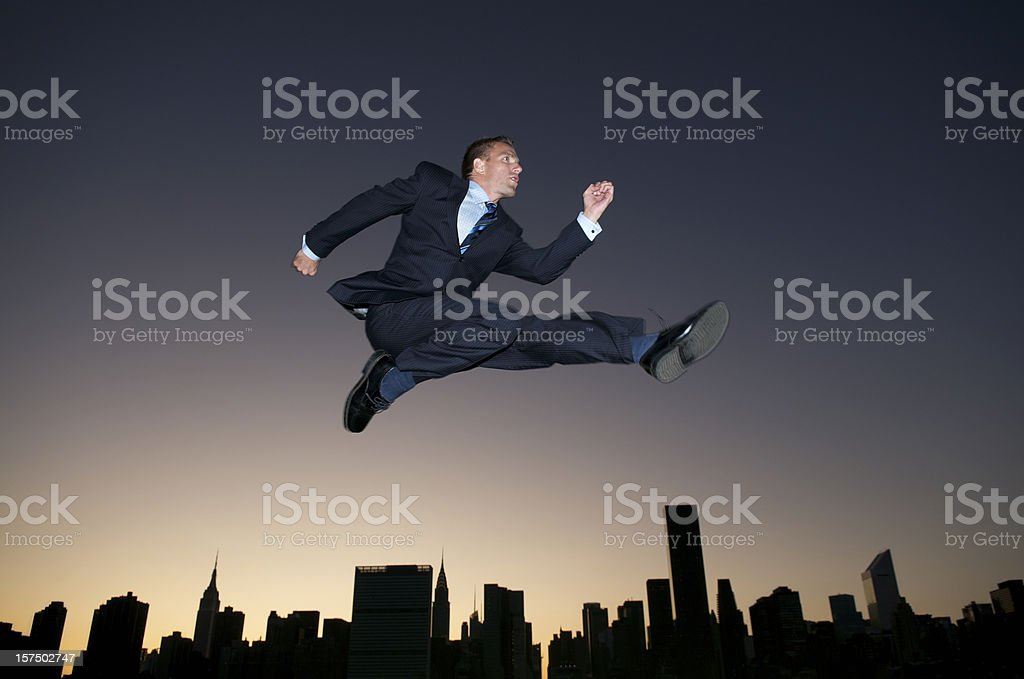 Businessman Leaps Over Sunset City Skyline Silhouette Dusk royalty-free stock photo