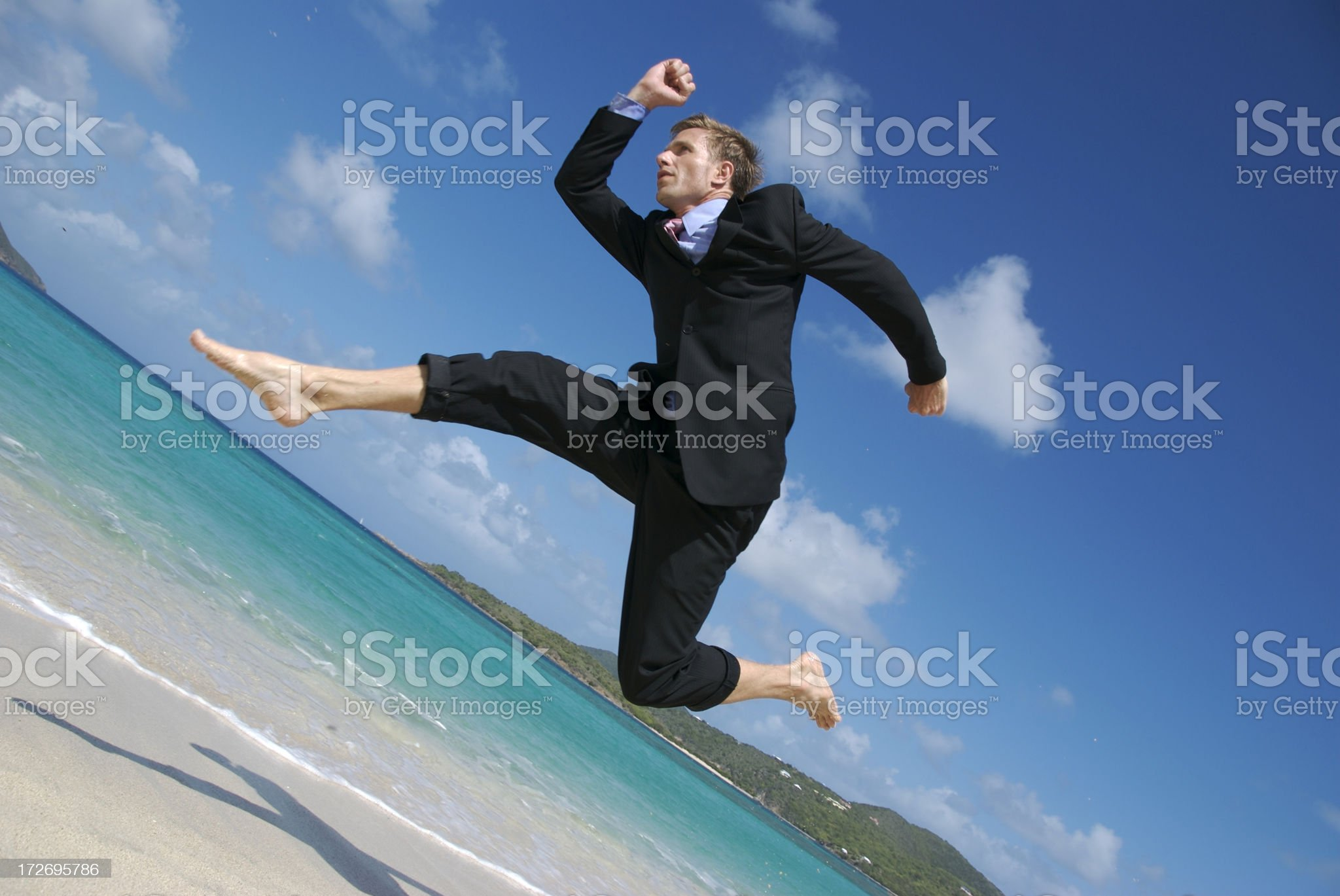 Businessman Leaps Over Tropical Beach royalty-free stock photo