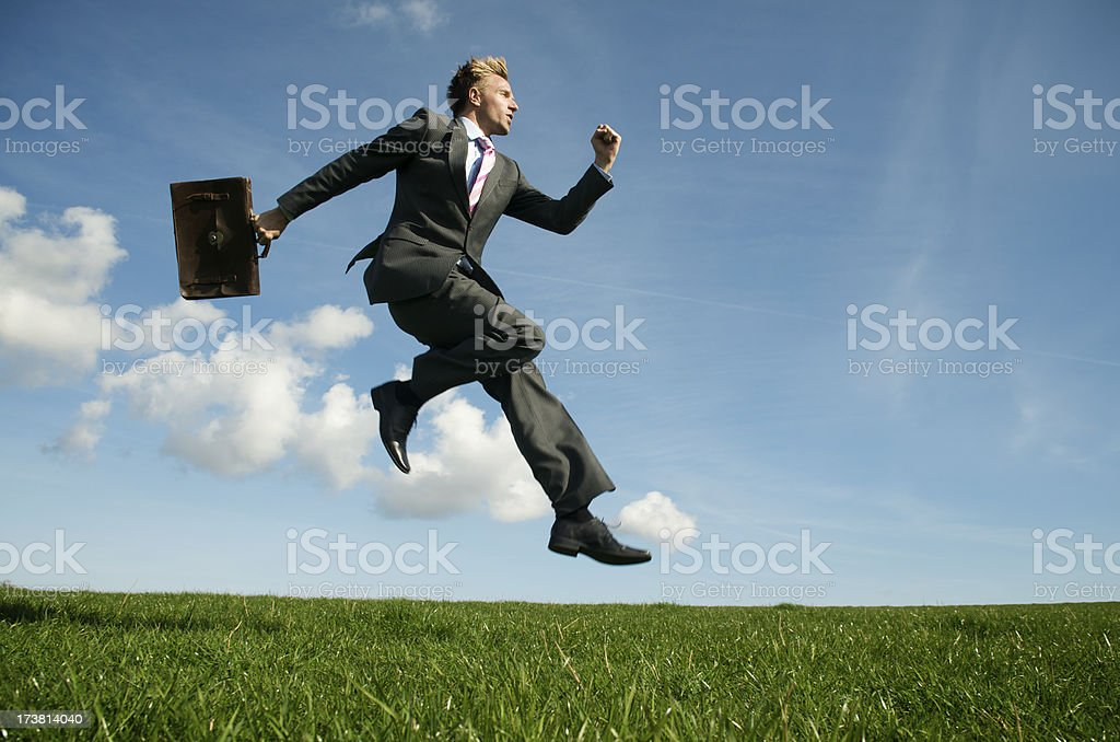 Businessman Leaps with Briefcase in Bright Green Meadow royalty-free stock photo