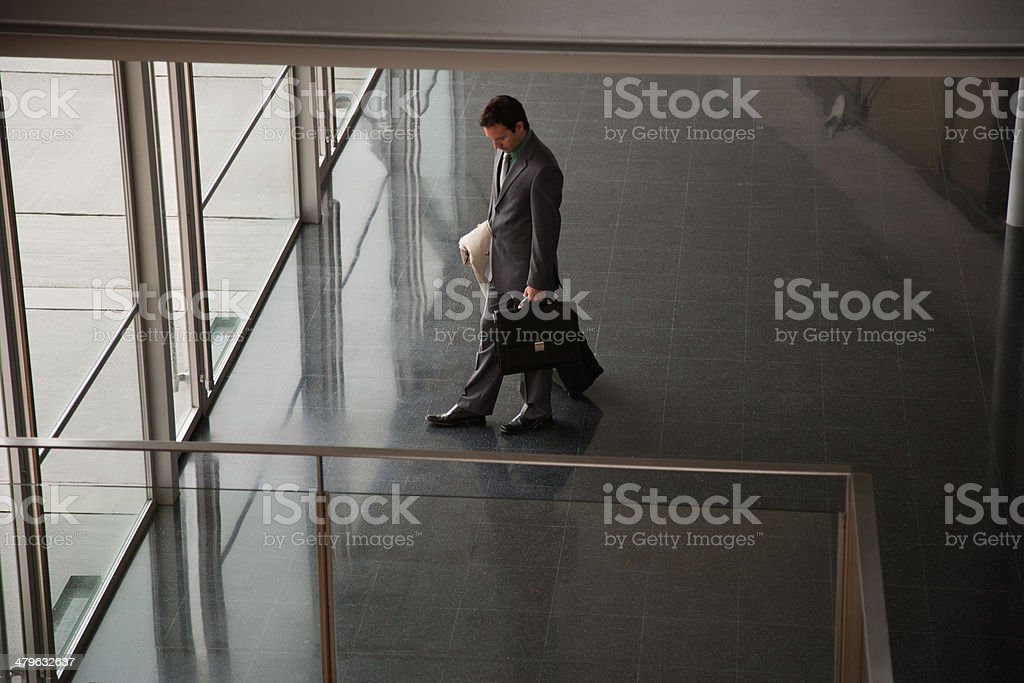 Businessman leaving building with suitcase stock photo