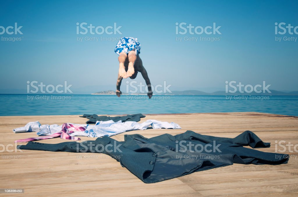 Businessman Leaving Suit Behind Diving into Water stock photo