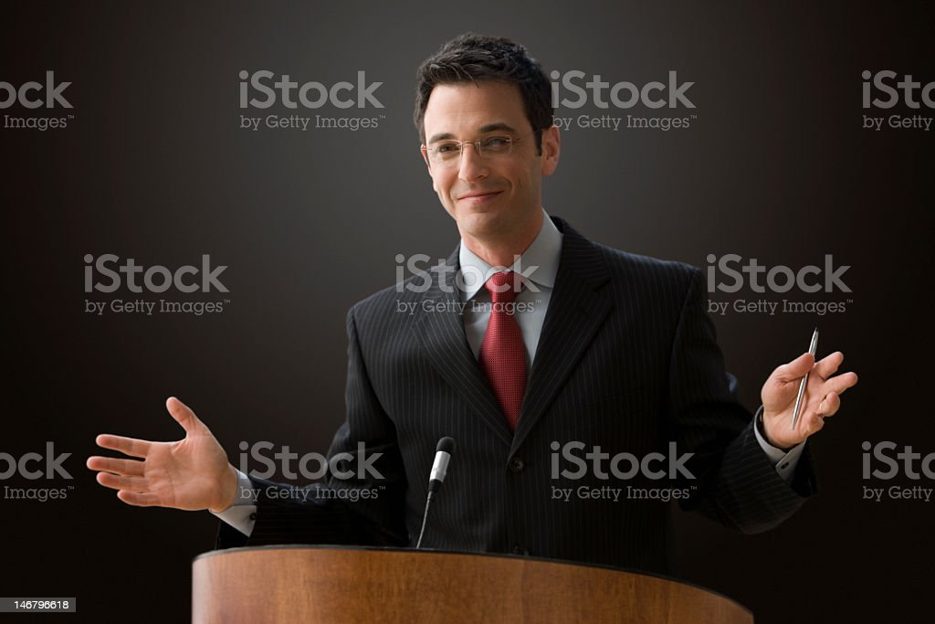 A businessman lecturing at a podium stock photo