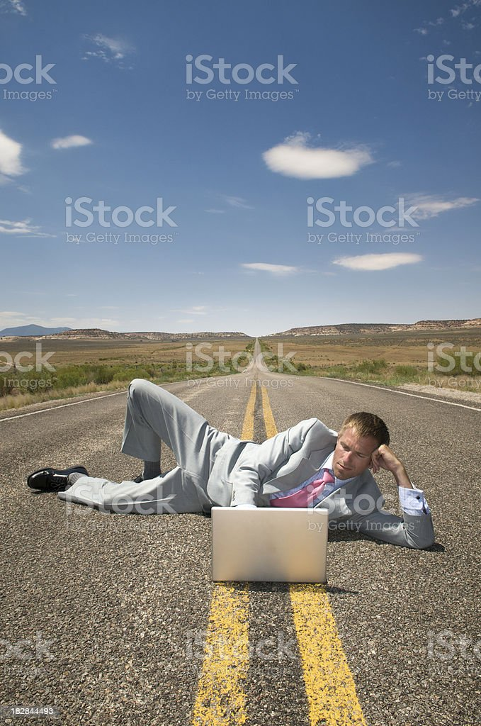 Businessman Lies Across Highway Working on Laptop royalty-free stock photo