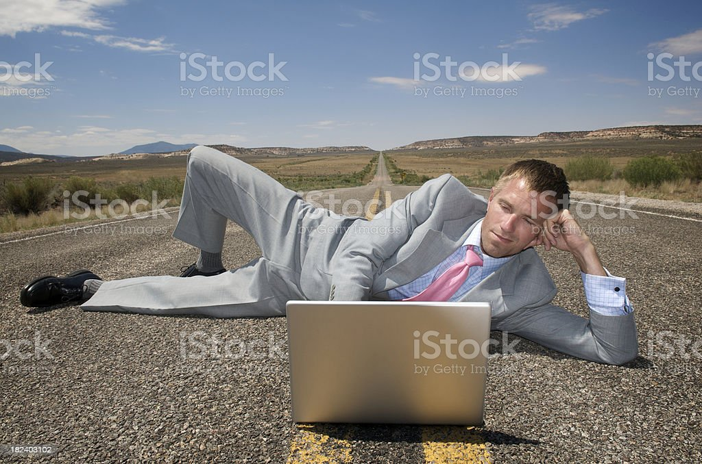 Businessman Lies on Highway w Laptop royalty-free stock photo