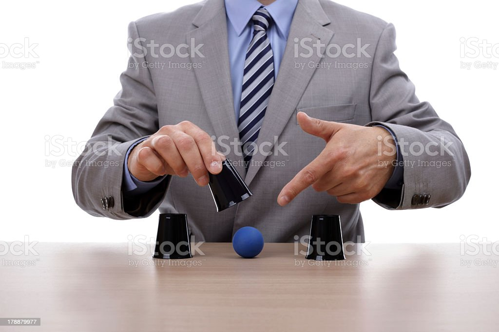 A businessman lifting the center of three cups and pointing stock photo