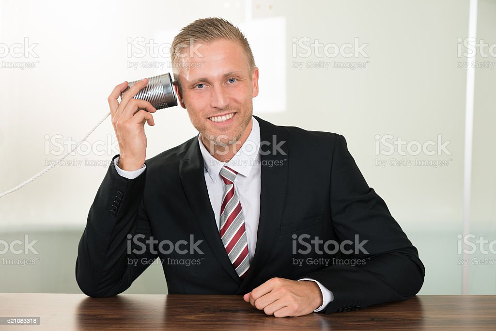 Businessman Listening From Tin Cans Phone stock photo