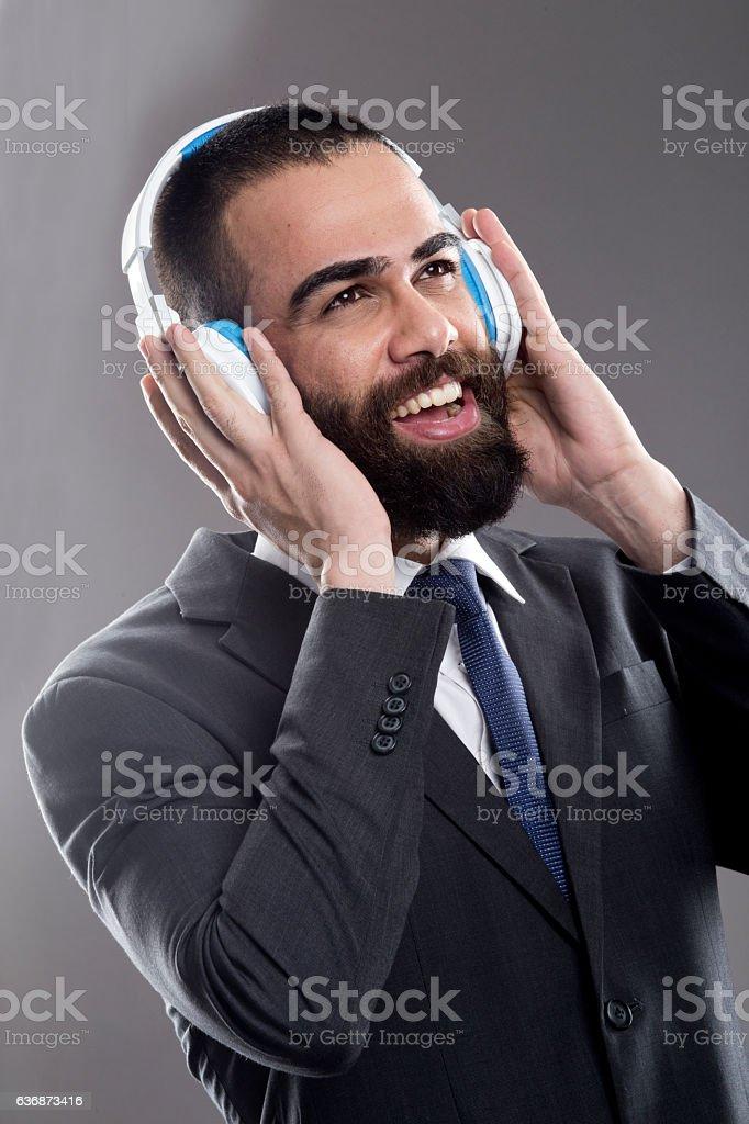 Businessman listening music on headphones stock photo