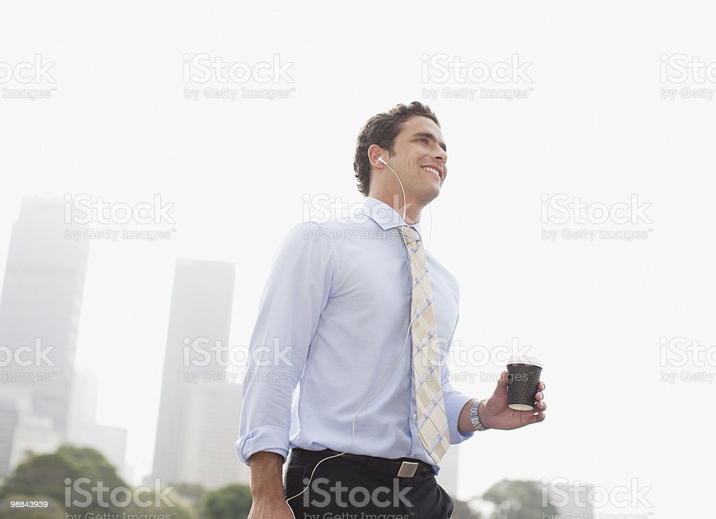Businessman listening to headphones and carrying coffee stock photo