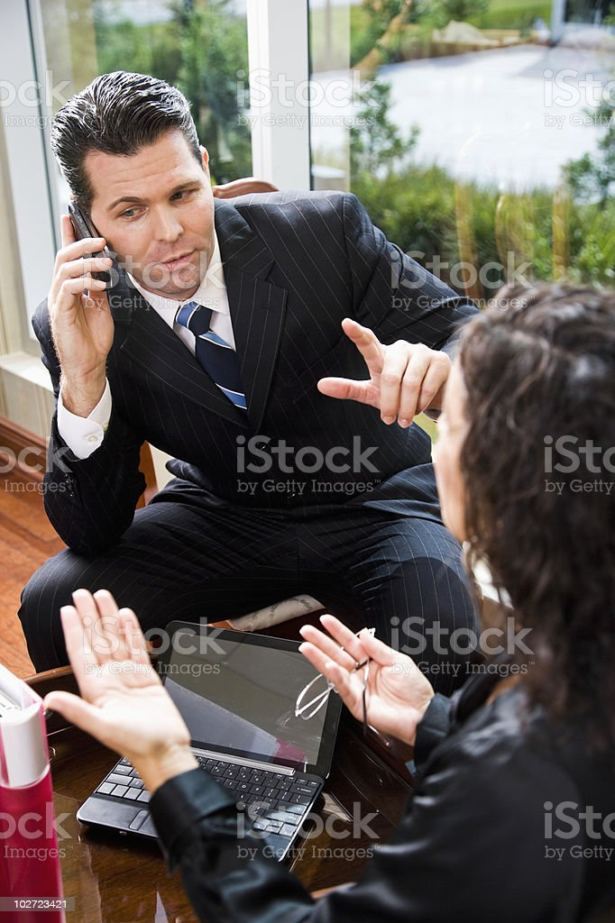 Businessman listening to mobile phone in meeting stock photo