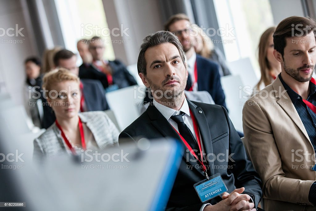 Businessman listening to presentation during seminar stock photo