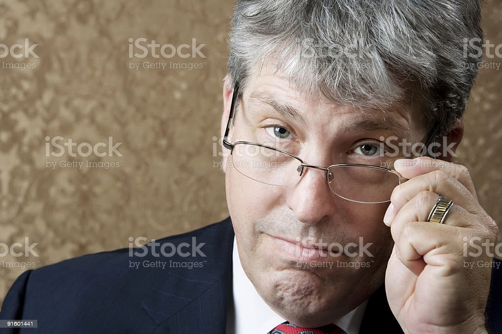 Businessman Lokking Over His Glasses stock photo