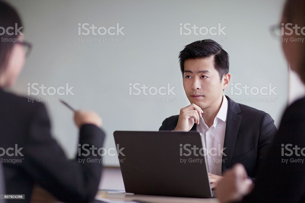 Businessman looking across table in office meeting stock photo