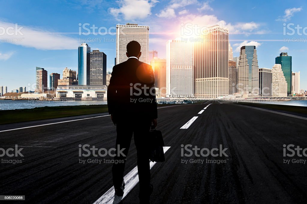 Businessman looking ahead on the road to the cityscape stock photo