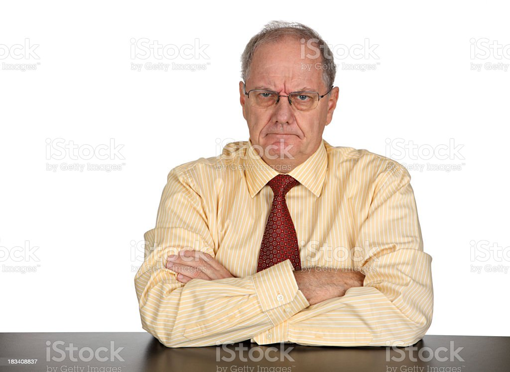 Businessman looking angrily at the camera with arms crossed stock photo
