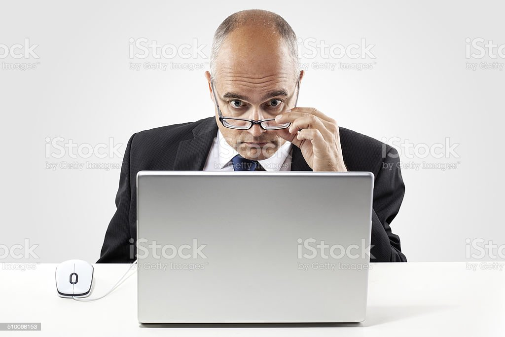 Businessman looking astonished at laptop screen stock photo