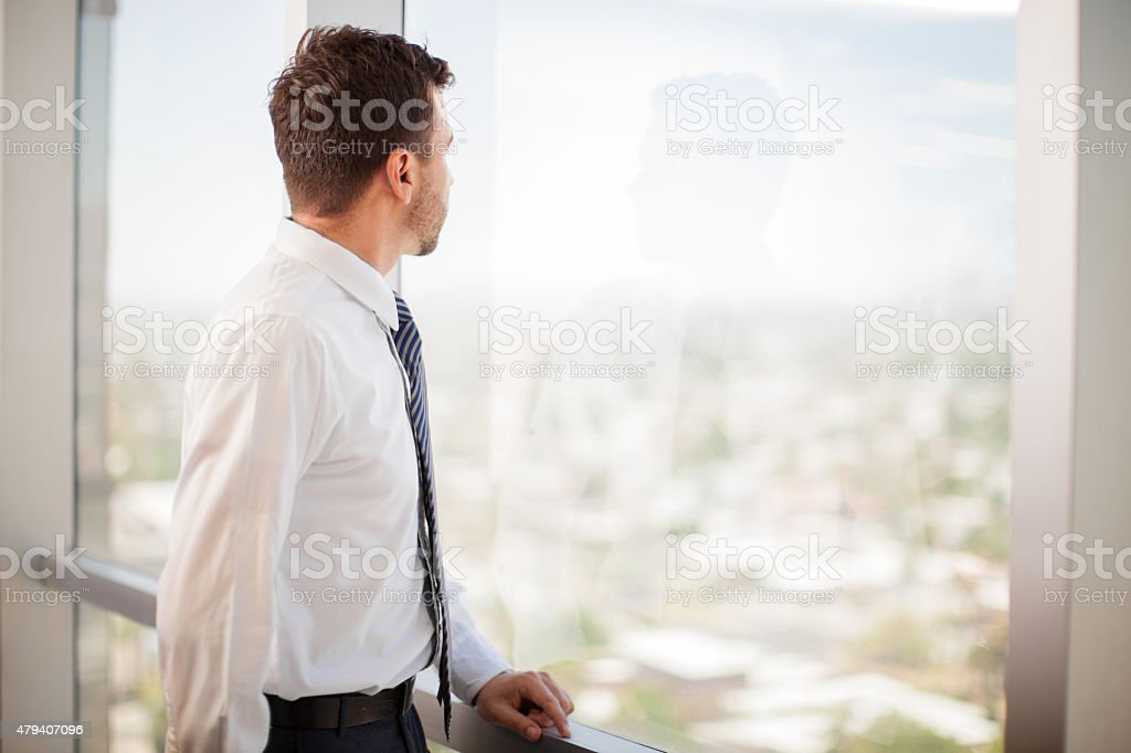 Businessman looking at a window stock photo