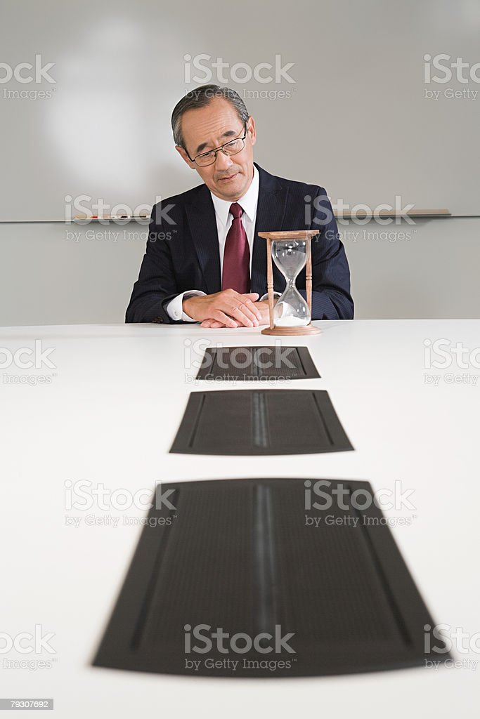 A businessman looking at an egg timer stock photo