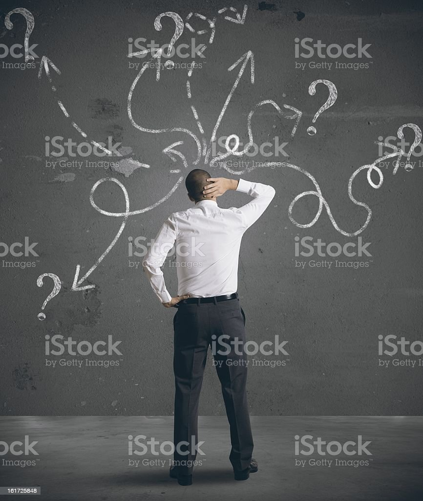 Businessman looking at arrows pointed in different directions stock photo