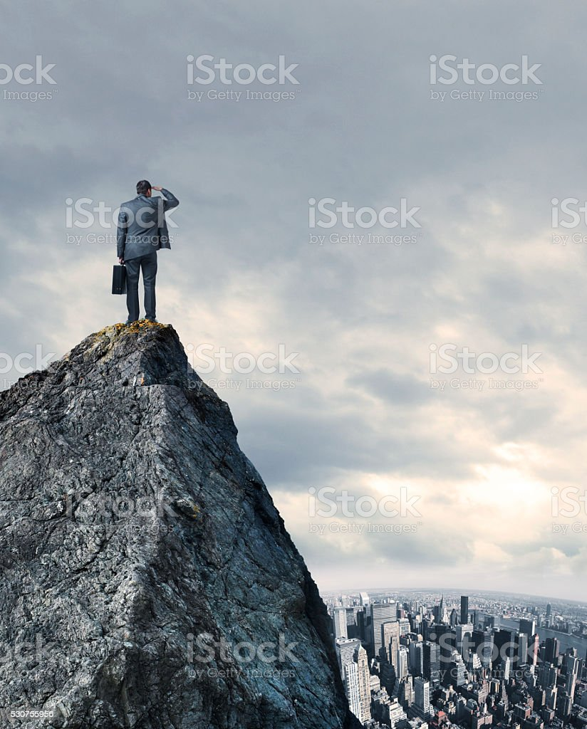 Businessman Looking At Big City While Standing On Mountain Top stock photo