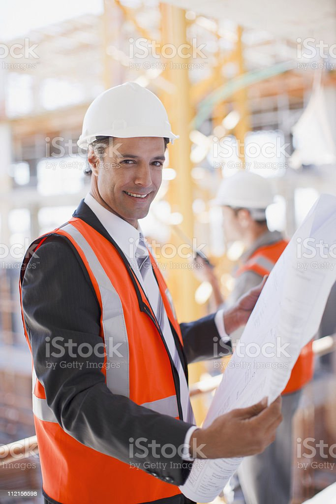 Businessman looking at blueprints on construction site royalty-free stock photo