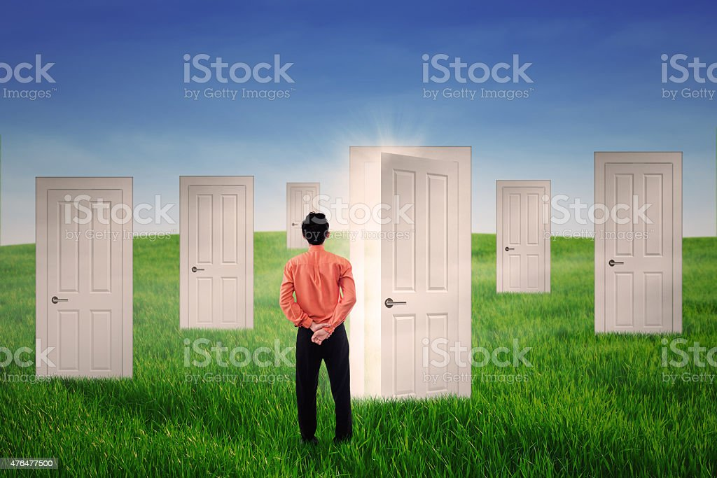 Businessman looking at bright door stock photo