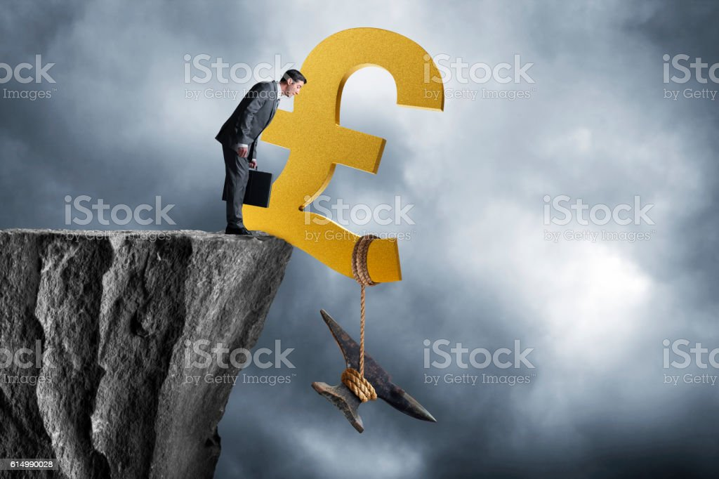 Businessman Looking At British Piound Weighed Down By Anvil stock photo