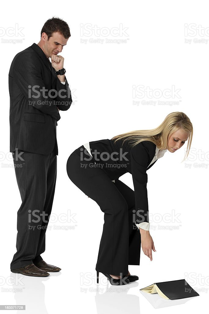 Businessman looking at businesswoman picking up a fallen book royalty-free stock photo