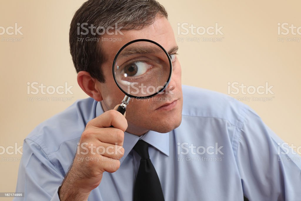 Businessman looking at camera through a magnifying glass stock photo