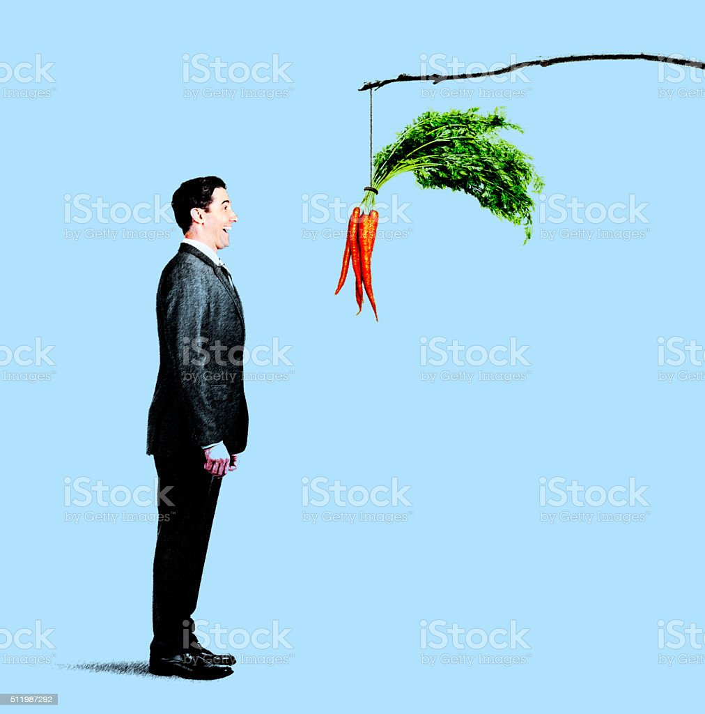 Businessman Looking At Carrots Dangling From Stick. stock photo