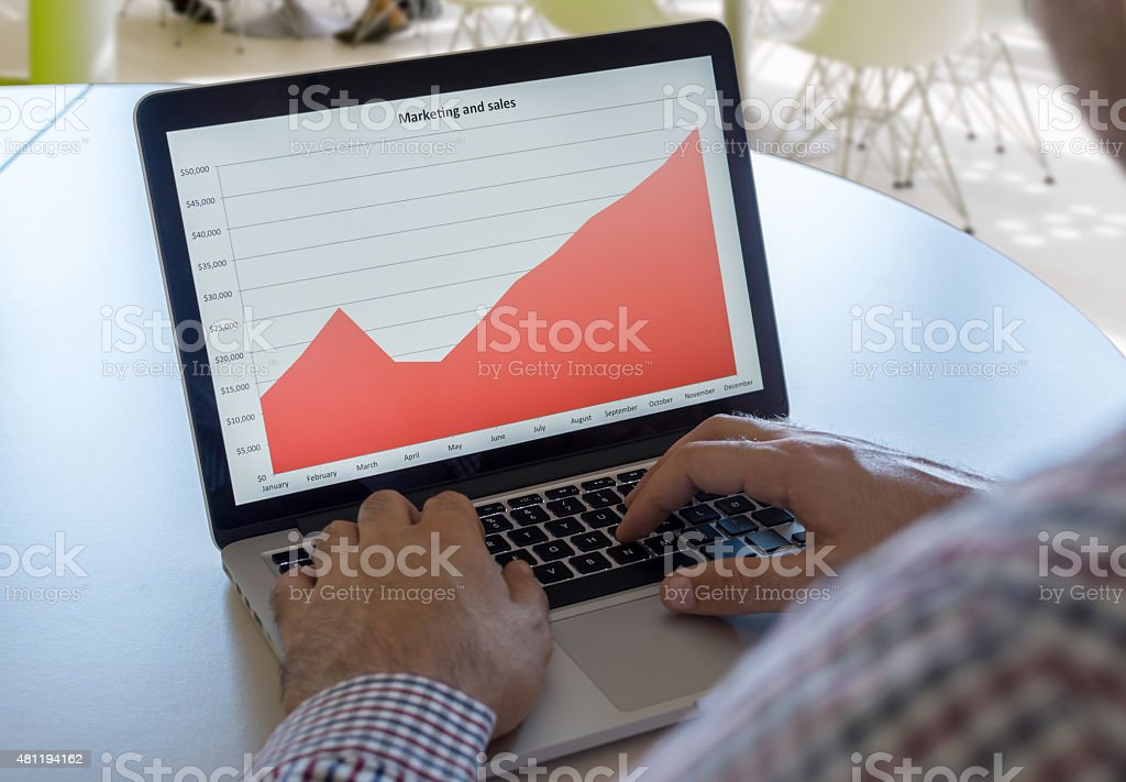 Businessman looking at chart on his laptop stock photo