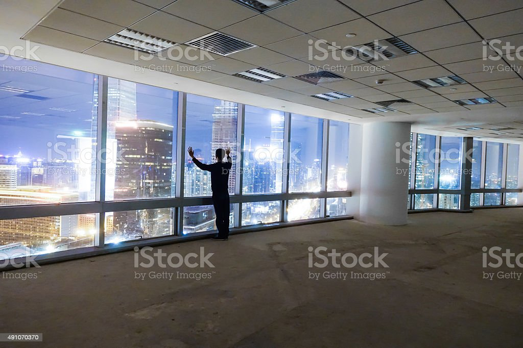 Businessman looking at cityscape at night stock photo