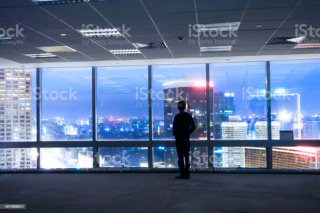 Businessman looking at cityscape from office window stock photo