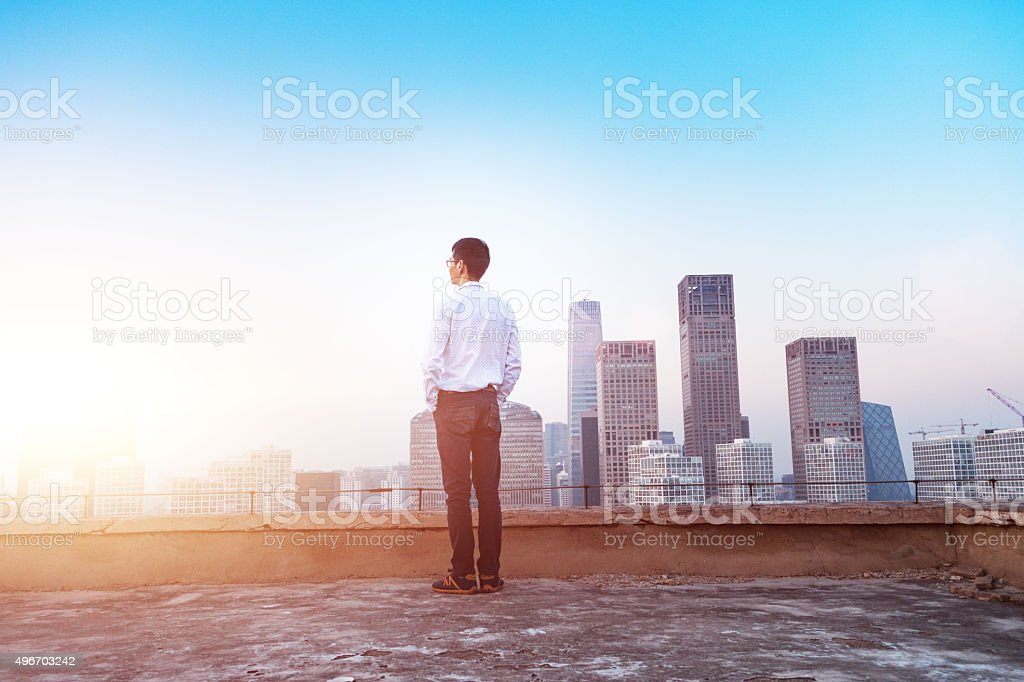 Businessman looking at cityscape with sunlight stock photo