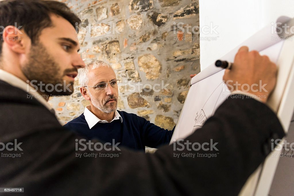 Businessman looking at coworker drawing on paper stock photo