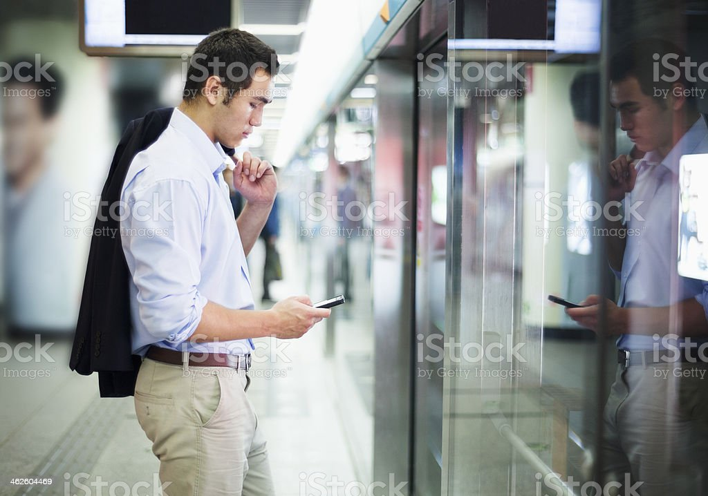Businessman looking at his phone and waiting for subway stock photo