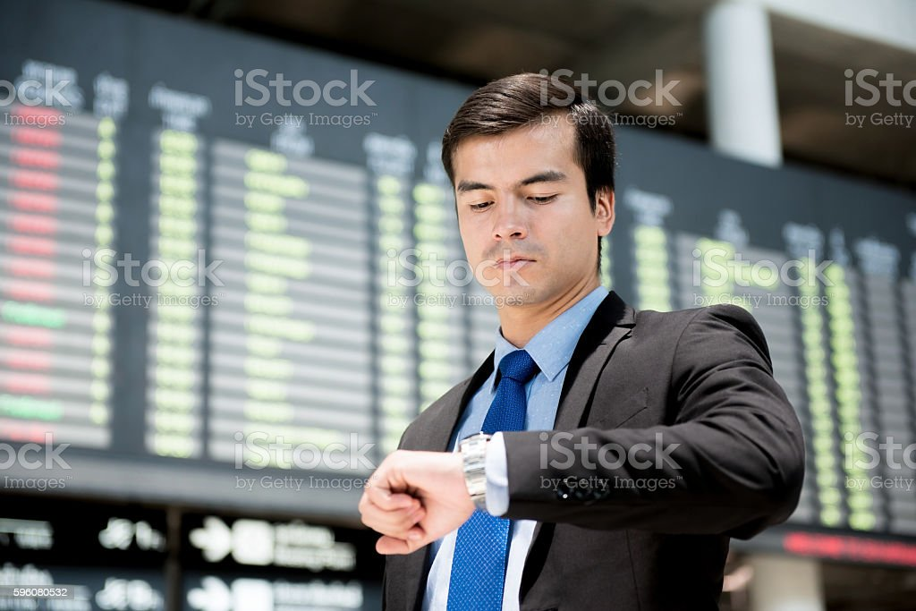 Businessman looking at his watch in front of airport timetable stock photo