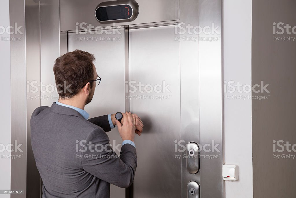 Businessman looking at his watch while waiting for the elevator stock photo