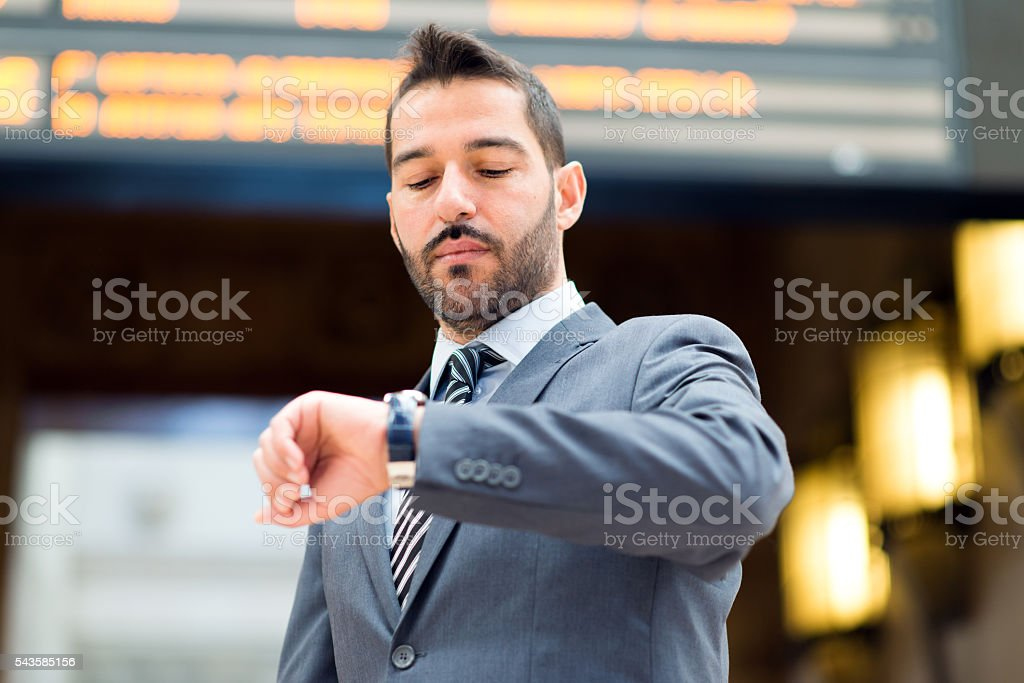 Businessman looking at his wrist watch stock photo