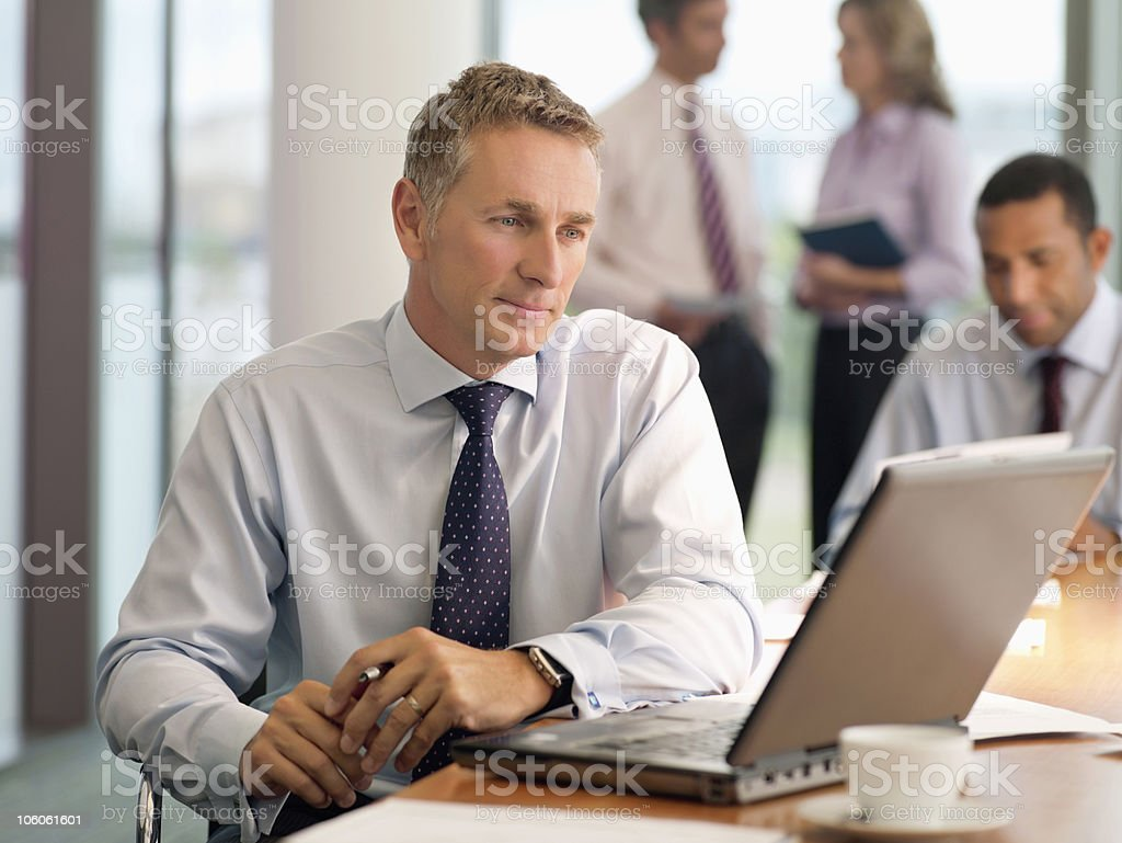 Businessman looking at laptop with executives in the background royalty-free stock photo