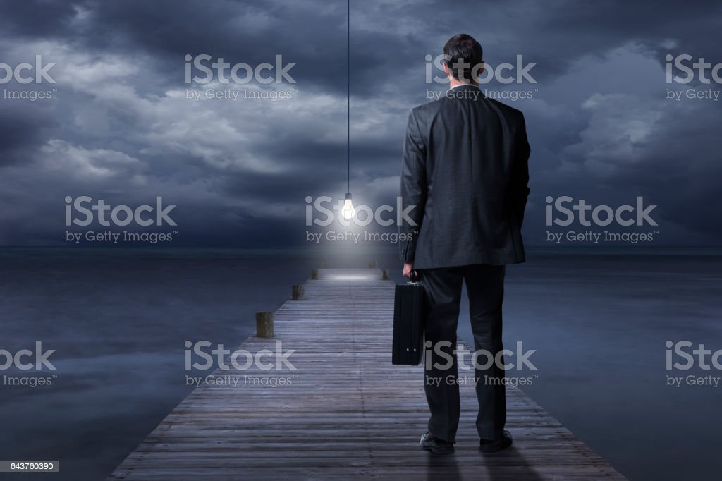 Businessman Looking At Light Bulb At End Of Pier stock photo