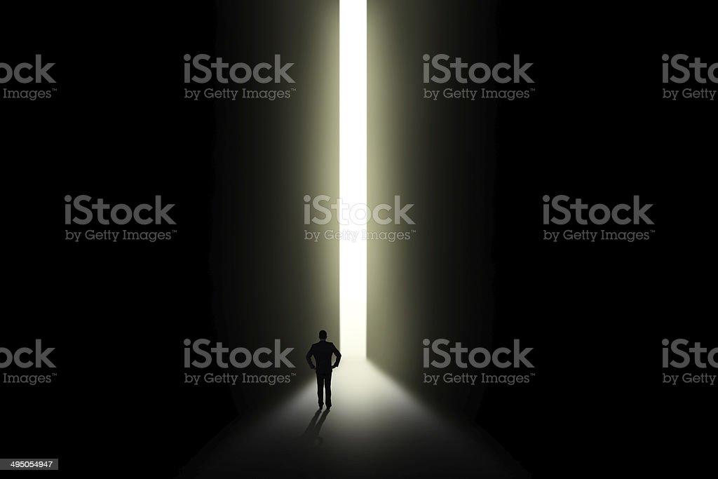 Businessman looking at light in doorway stock photo